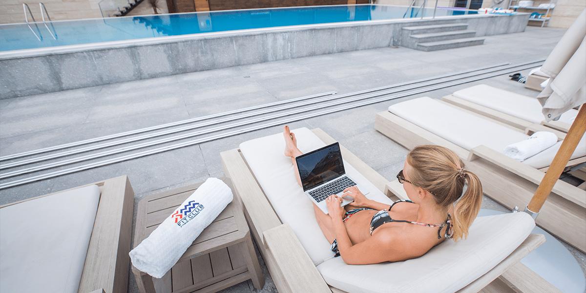 Mädchen mit Laptop am Pool